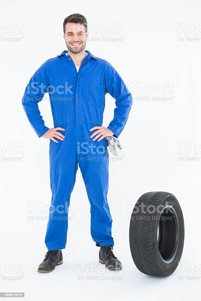 Smiling mechanic with hands on hips standing by tire stock photo