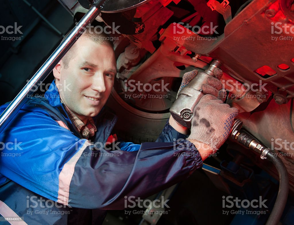 Smiling mechanic working under car in workshop royalty-free stock photo