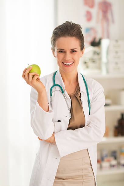 smiling medical doctor woman with apple stock photo