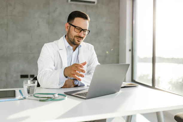 Smiling medical expert having a video call over laptop in the office. stock photo