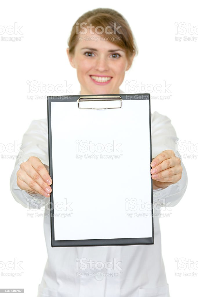 Smiling medical female doctor holding blank clipboard in hands royalty-free stock photo