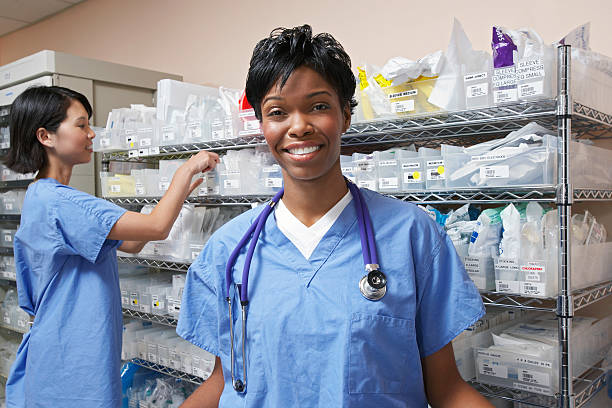 smiling medical professional and working staff in background - medical supplies stock photos and pictures