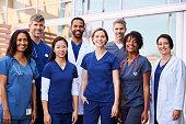 Smiling medical team standing together outside a hospital