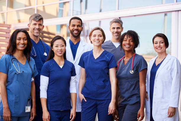 smiling medical team standing together outside a hospital - healthcare and medicine stock pictures, royalty-free photos & images