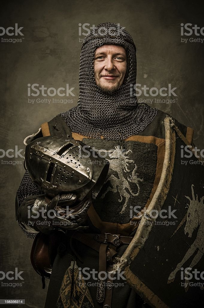 Smiling medieval knight  holding helmet stock photo