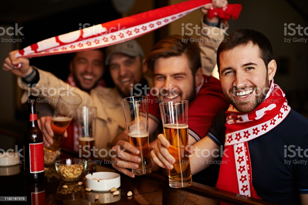 Happy fans with beer glasses showing scarf of favorite sport team...