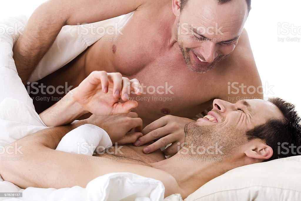 Smiling men couple in bed stock photo