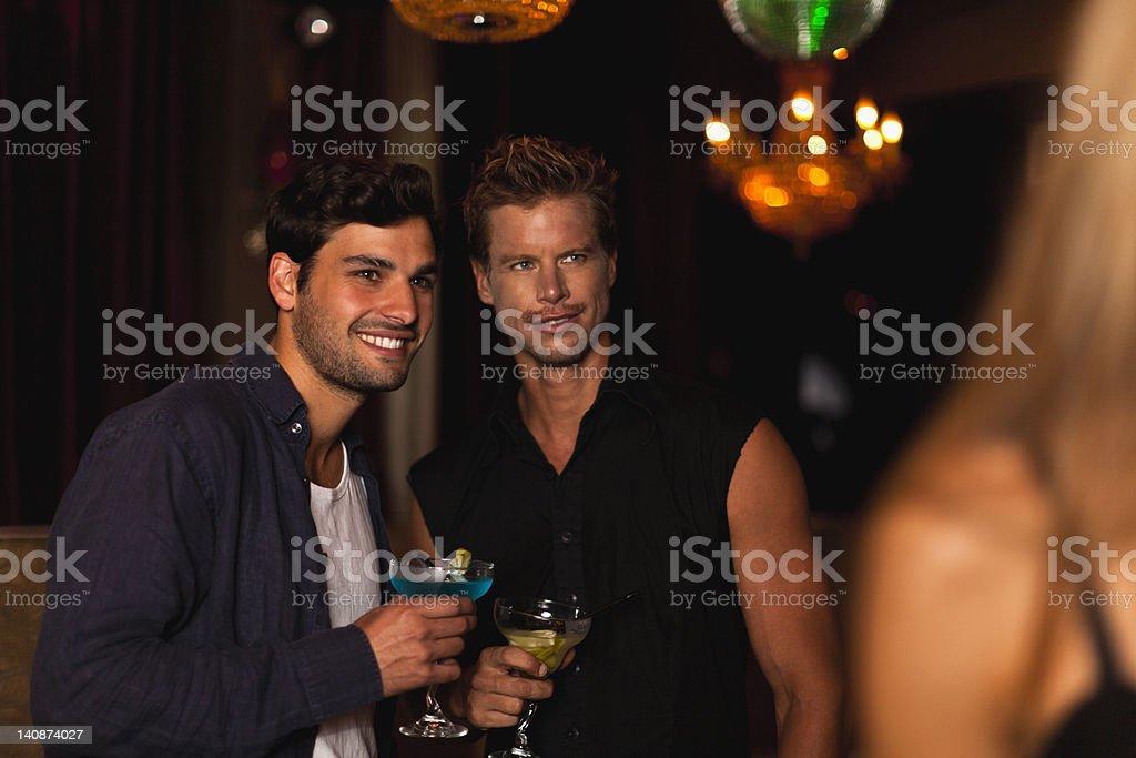 Smiling men having cocktails in club stock photo