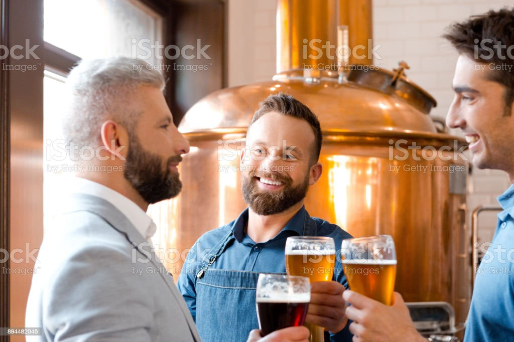 Smiling men toasting beers at micro brewery. Smiling men toasting beers at micro brewery. Team of three people toasting beer glasses at brewery. Adult Stock Photo