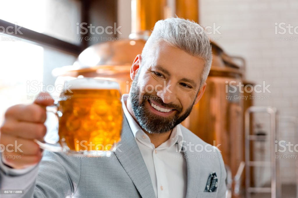 Smiling microbrewery owner holding a beer mug in his pub Smiling microbrewery owner holding a beer mug in his pub. Businessman looking at fresh beer glass at his brewery. Adult Stock Photo