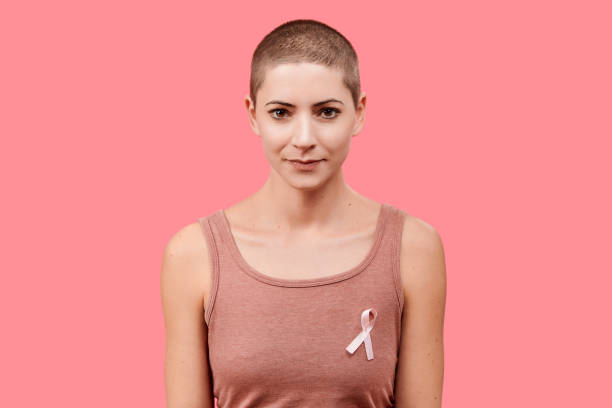 Smiling mid 30s woman, a cancer survivor, wearing pink breast cancer awareness ribbon, isolated over living coral background. Support, solidarity, screening and prevention concept. Smiling mid 30s woman, a cancer survivor, wearing pink breast cancer awareness ribbon, isolated over living coral background. Support, solidarity, screening and prevention concept. shaved head stock pictures, royalty-free photos & images