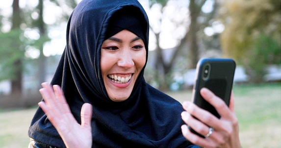 Smiling mid adult asian muslim woman wearing a hijab looking at her smart phone