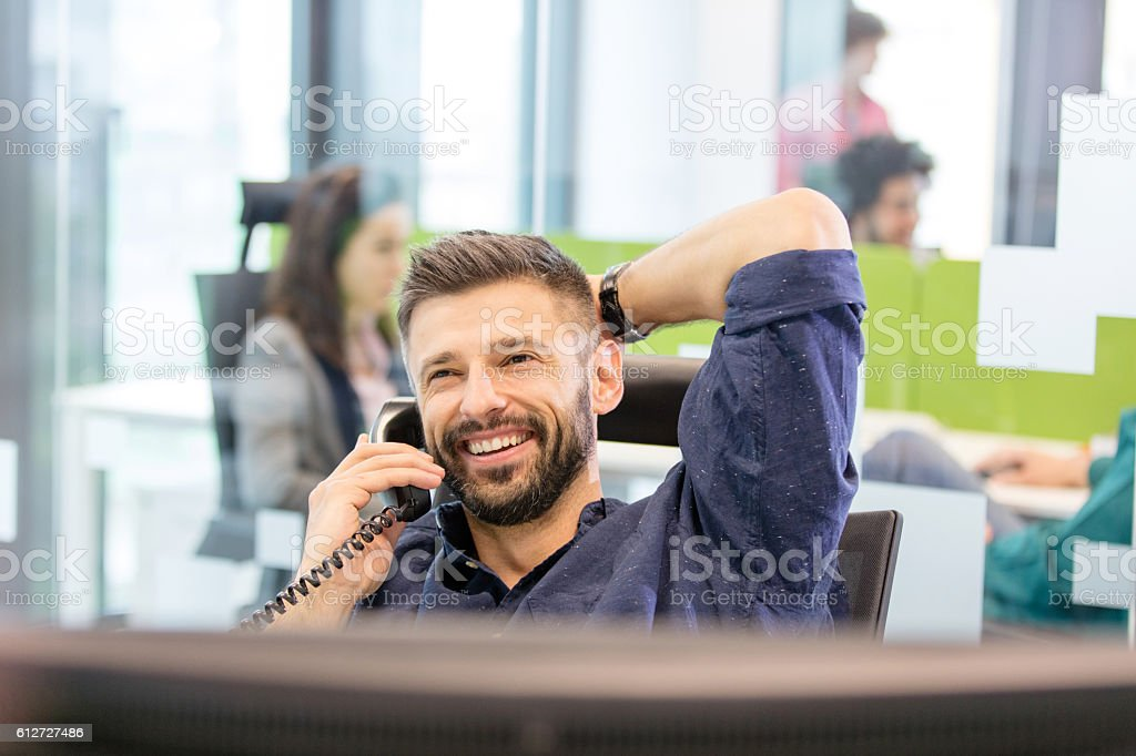 Smiling mid adult businessman talking on phone in office stock photo