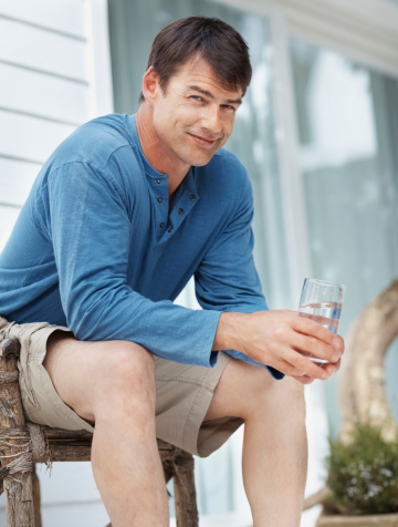 Smiling Mid Adult Guy With A Glass Of Water Stock Photo - Download Image Now