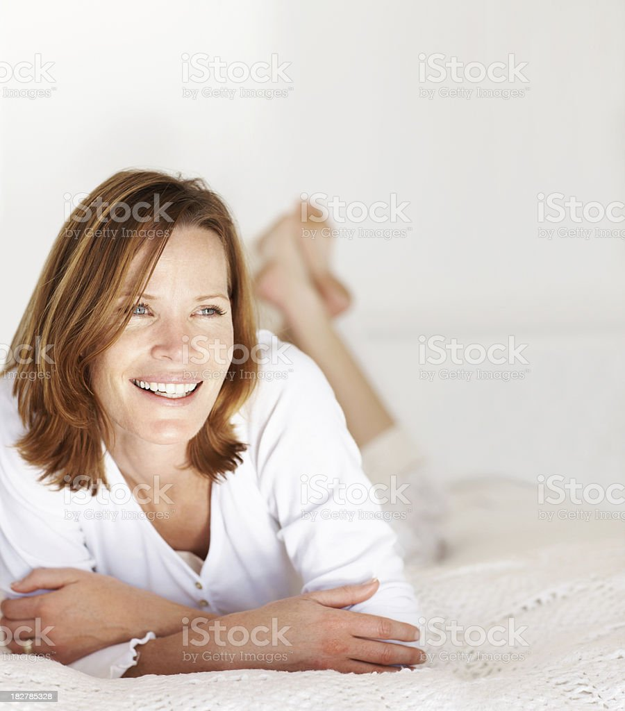 Smiling mid adult lady lying on bed at home royalty-free stock photo