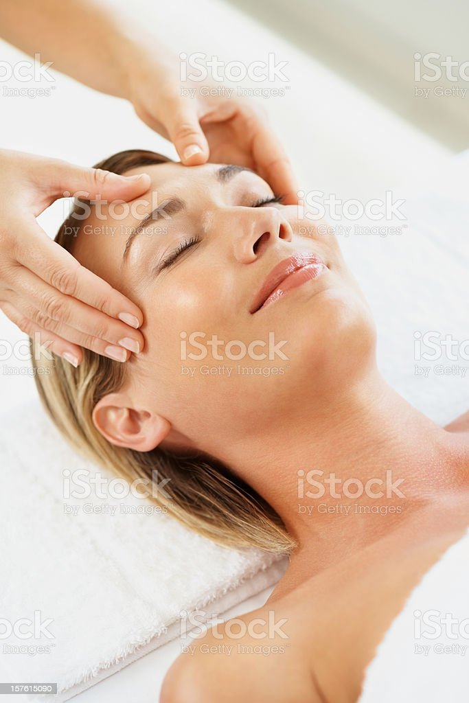Smiling mid adult lady receiving head massage in spa royalty-free stock photo