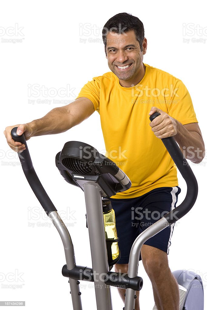Smiling mid adult man working out on elliptical machine royalty-free stock photo