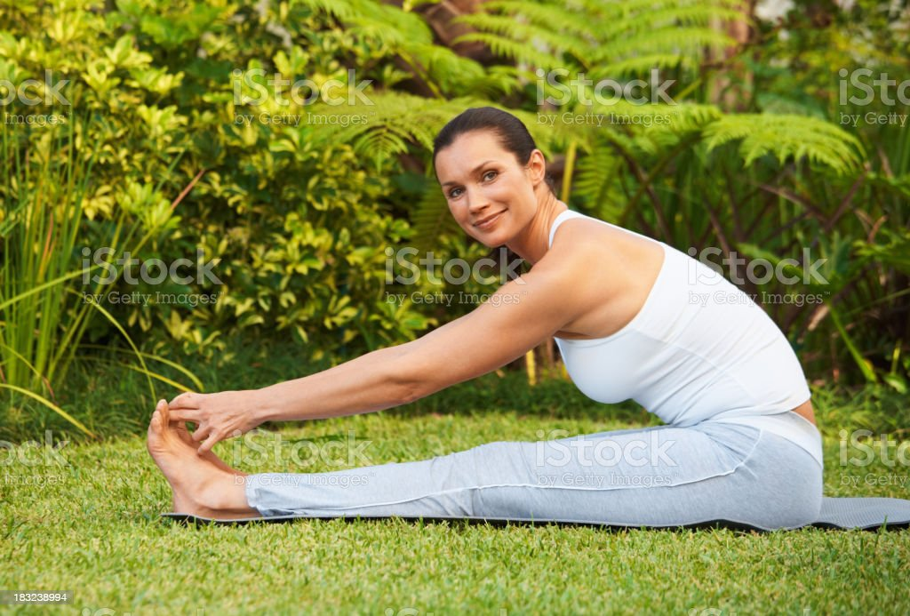 Smiling mid adult woman doing stretching exercise on lawn royalty-free stock photo