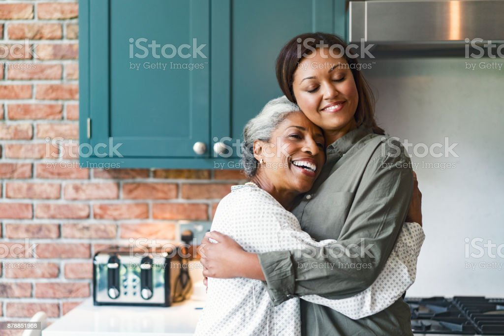 Smiling mid adult woman embracing senior mother stock photo