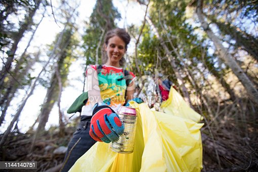 Smiling Mid Adult Woman Picking Up Trash in Forest.