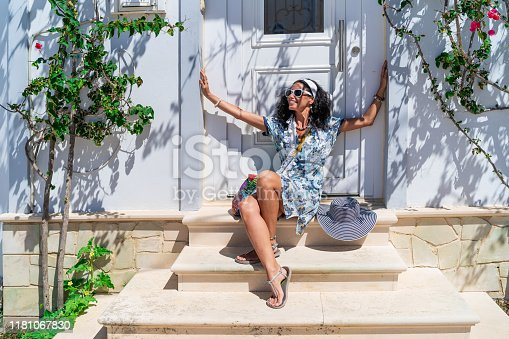 Smiling mid adult woman sitting in front of old house in old town Volimes in Zakynthos Greece