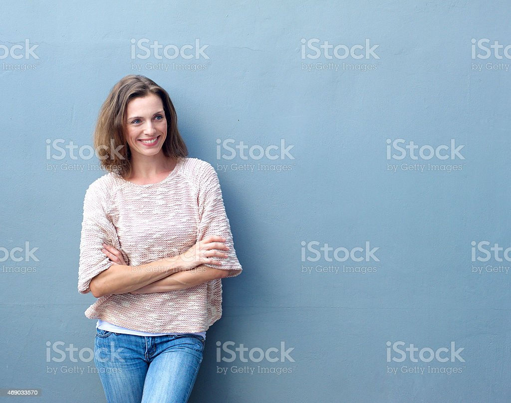 Smiling mid adult woman standing with arms crossed stock photo