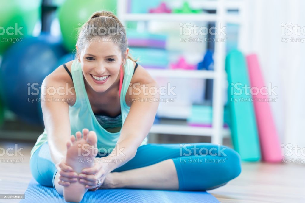 Smiling mid adult woman stretches leg on floor at local gym stock photo