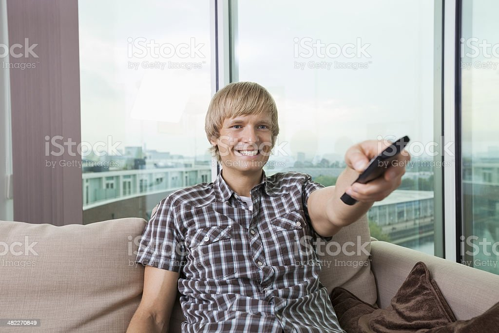 Smiling mid-adult man watching television on sofa at home stock photo