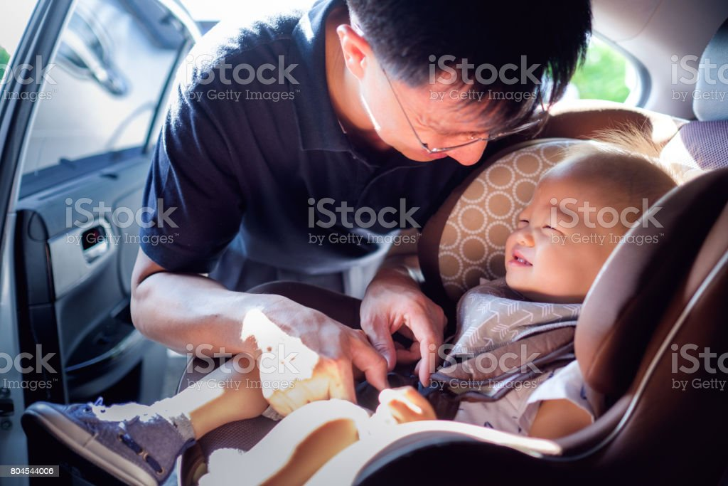 Smiling Middle age asian father helps his cute little asian 1 year old toddler baby boy child to fasten belt on car seat stock photo