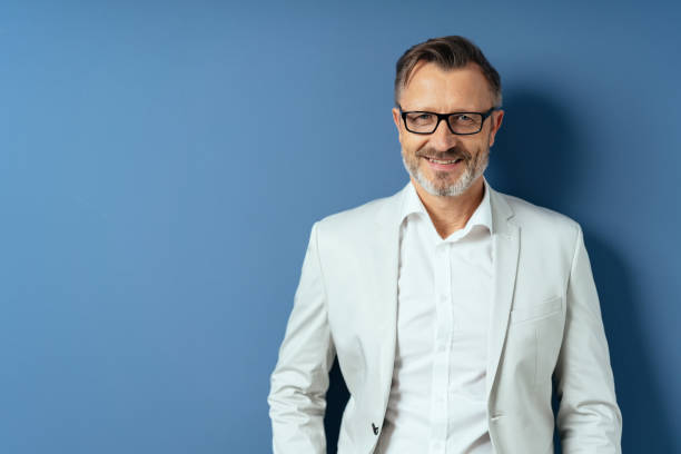 Smiling middle age man in glasses on blue stock photo