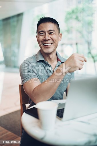 Smiling Asian ethnicity man using laptop in cafe