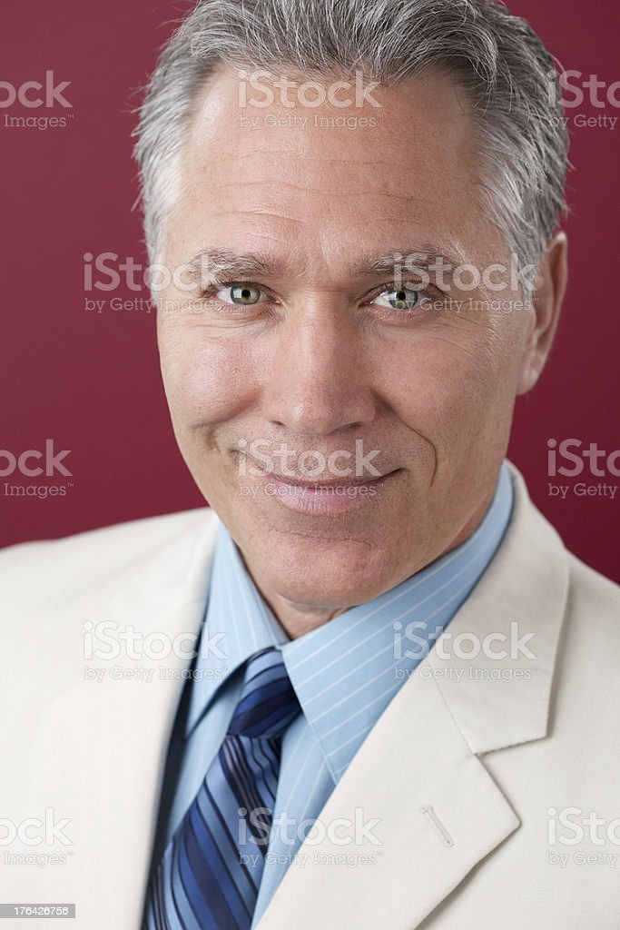Smiling middle age man with white suit coat royalty-free stock photo