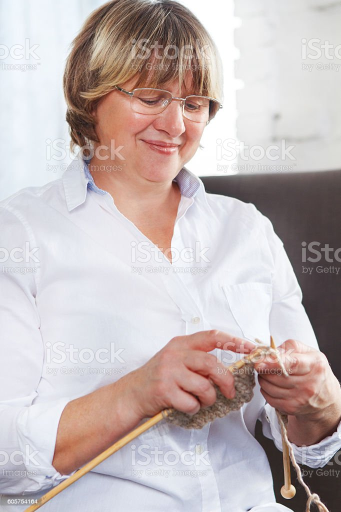 Smiling middle age woman knitting on spokes at home stock photo