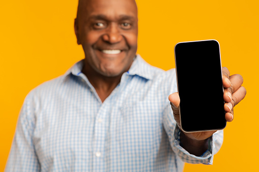 istock Smiling middle aged afro american man showing cellphone 1208750588