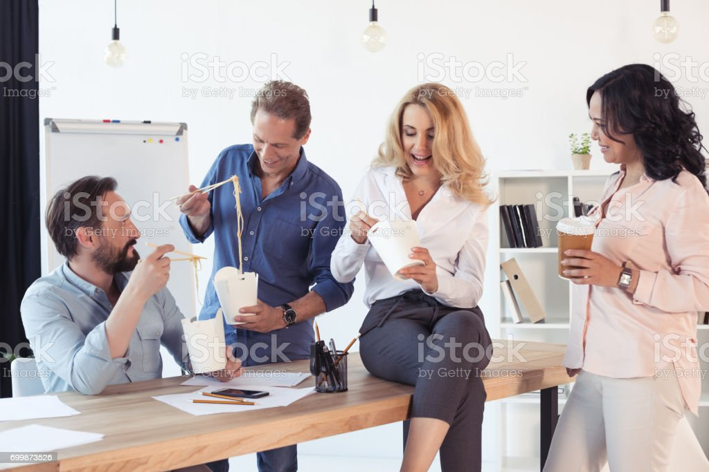 Smiling middle aged businessmen and businesswomen eating asian food in office stock photo