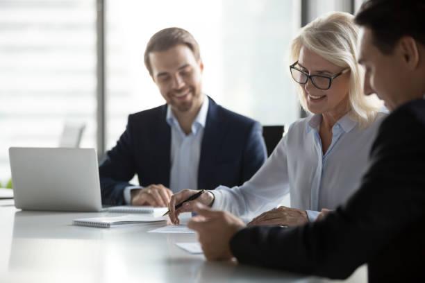 glimlachend midden leeftijd zakenvrouw ondertekening papier contract bij fractievergadering - notaris stockfoto's en -beelden