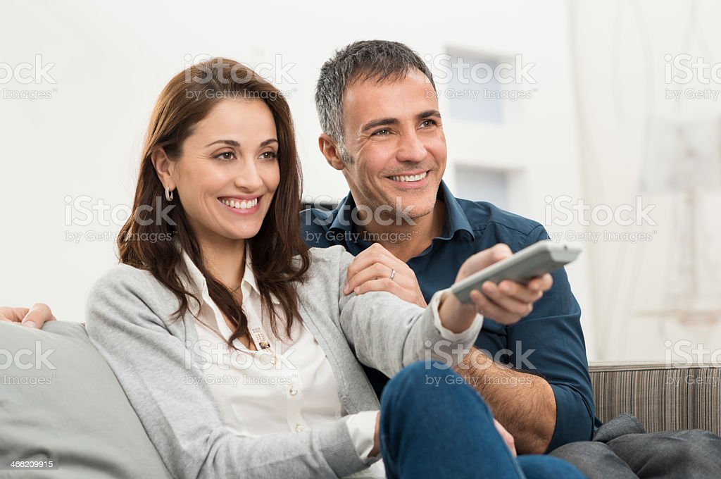 Smiling middle aged couple watching television on the couch stock photo
