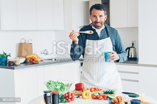 istock Smiling middle aged man cooking 924202114