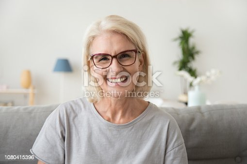 istock Smiling middle aged mature grey haired woman looking at camera 1080415396