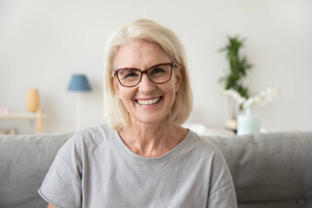 Smiling middle aged mature grey haired woman looking at camera stock photo