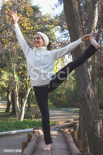 Female mature yogi on wooden path with extended hand to big toe pose. Fall season, sport activity in the park