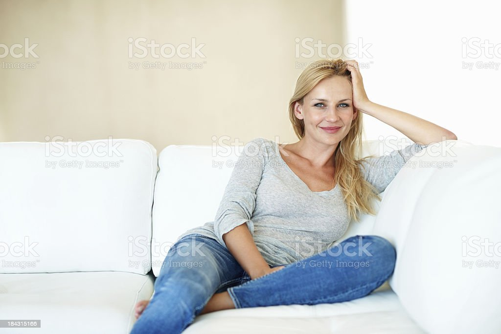 Smiling middle aged woman on couch royalty-free stock photo