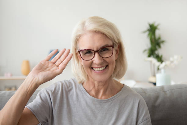 Smiling middle aged woman waving hand looking at camera, portrait stock photo