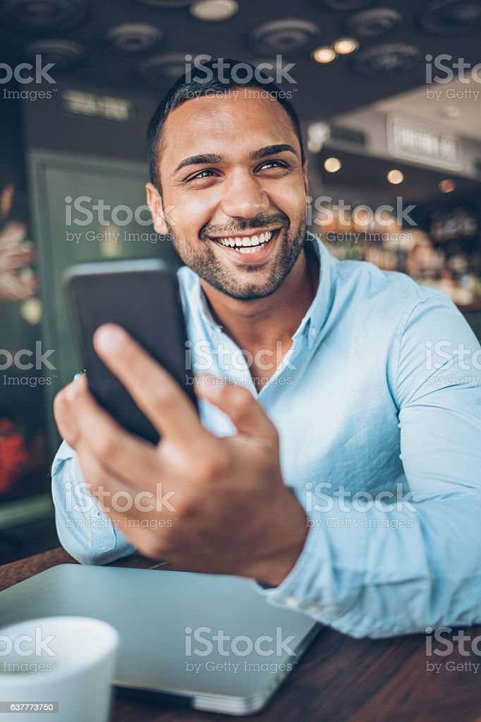 Cheerful young man with smart phone and laptop in cafeteria.