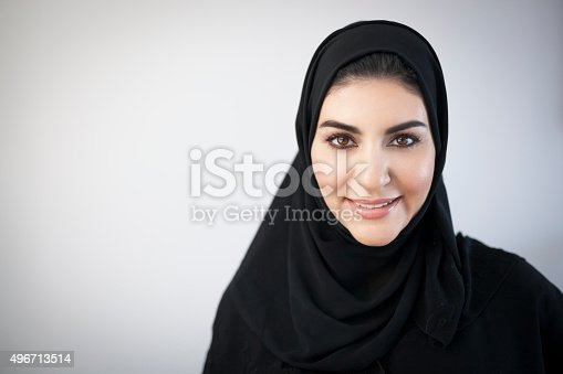 Young middle eastern woman dressed in black religious veil pleasantly smiling and looking at the camera. Dark brown eyes and hair, glowing skin, warm look. Light grey background darkened around the corners. Image contains plenty of copy space on the left. Made in Dubai, United Arab Emirates.
