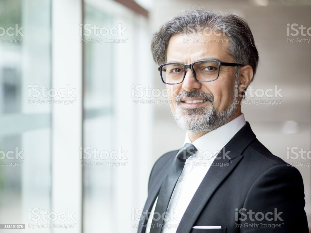 Smiling Middle-aged Business Leader at Window stock photo