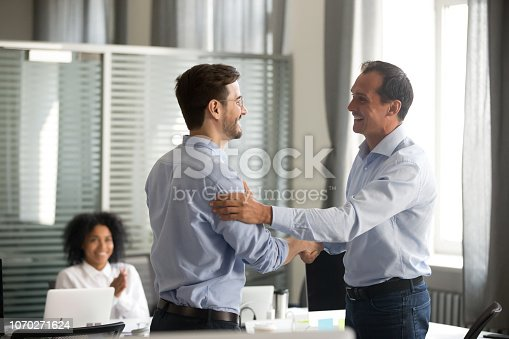 istock Smiling middle-aged ceo handshaking successful male worker showing respect 1070271624