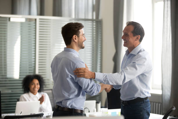 Smiling middle-aged ceo handshaking successful male worker showing respect stock photo