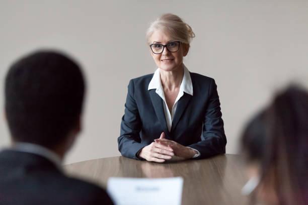 lächelnd im mittleren alter weiblicher job bewerber machen ersten eindruck im interview - vorurteil stock-fotos und bilder