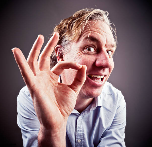Smiling middle-aged man gives approving OK hand signal A smiling, slightly goofy-looking middle-aged man gives an approving OK hand signal. approbation stock pictures, royalty-free photos & images